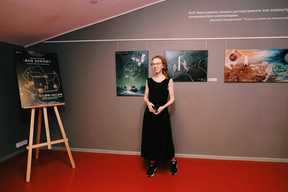 "Anastasia Prosochkina in front of her paintings at the museum. Exhibition project ""Outside the Earth?"" from the cycle ""Space in Art"". Photo from the exhibition opening."