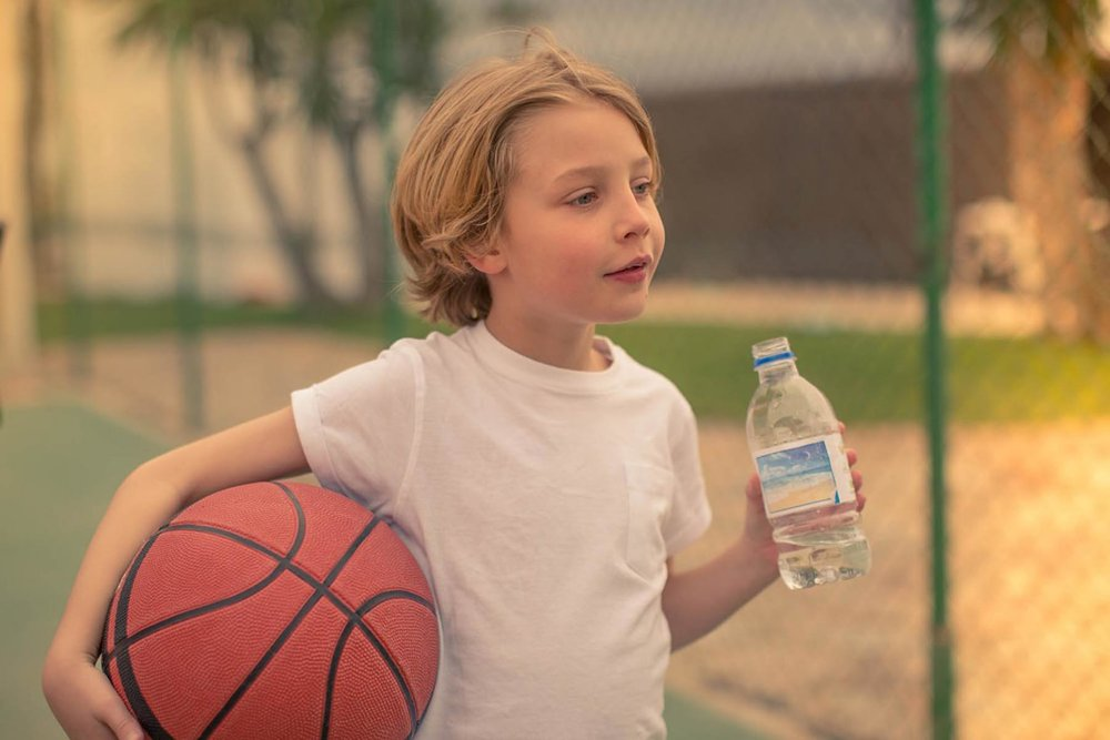 Richard Wadey Child Holding Ball & Bottle of Water