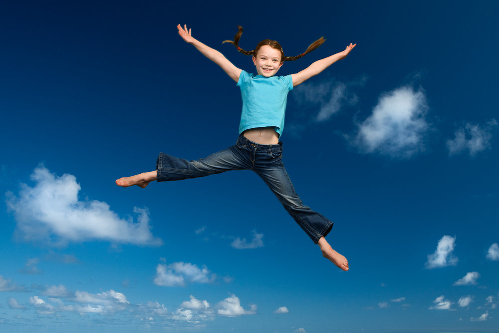 Tim Platt - Girl jumping with blue sky background