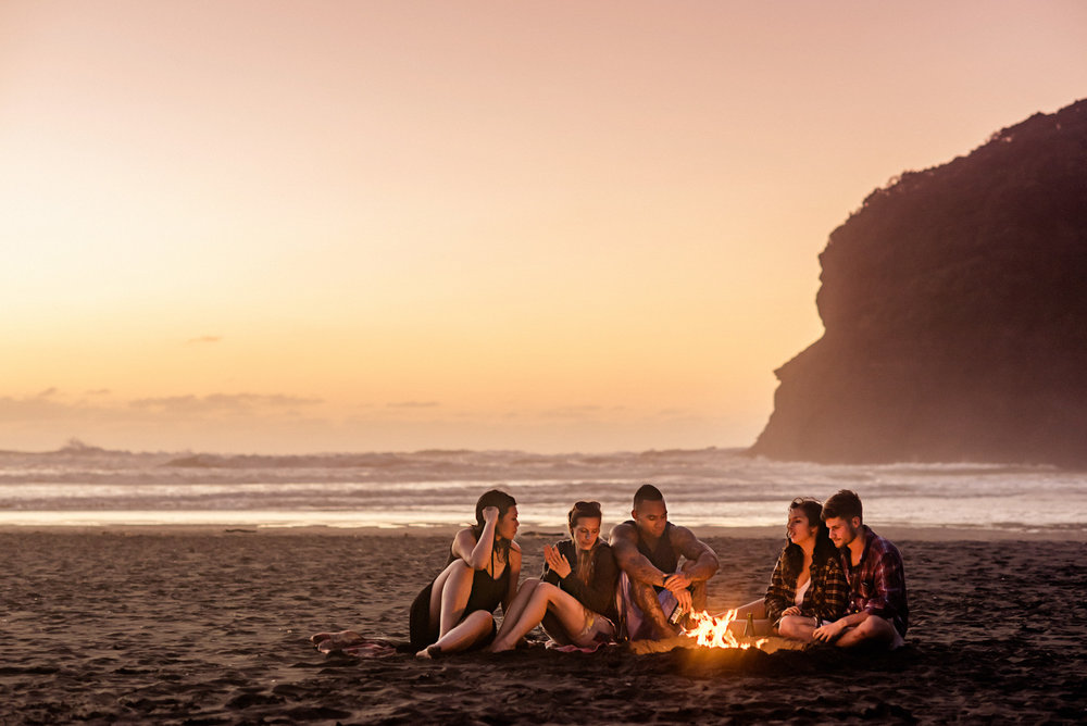 Matthew Joseph - group on beach at sunset around camp fire