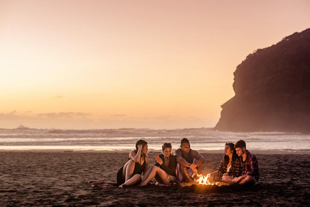 Matthew Joseph - group on beach at sunset around camp fire