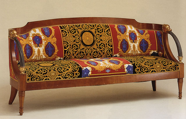 A Continental Neoclassical Style Mahogany and Parcel-Gilt Settee, upholstered in Gianni Versace designed cotton velvet 'Gold Vanitas' and 'Petitot' pattern