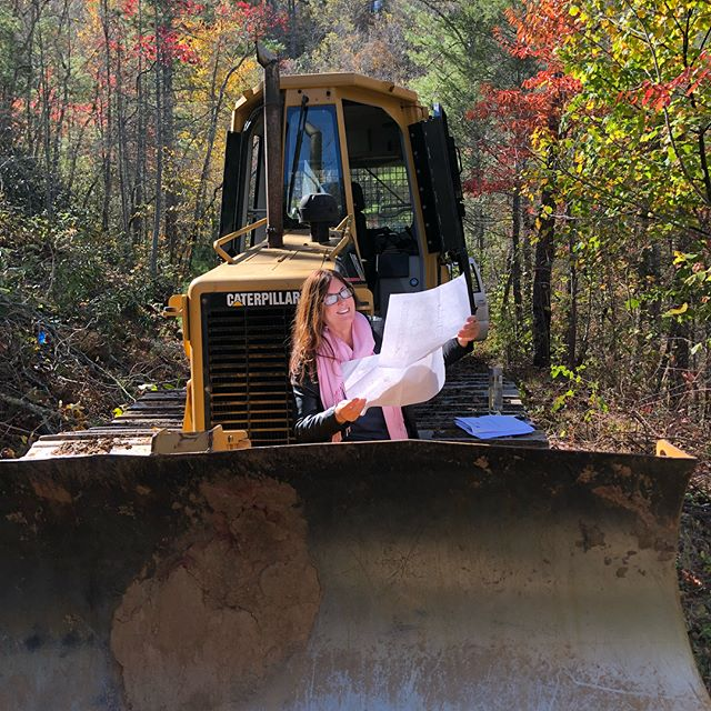 Joy checks our plans one last time... let's get it on! The new HQ is underway!! . Second photo is the beginning of our driveway, which is actually an old logging road. . Now we are moving dirt!!! . . . . #waterstone #construction #greenconstruction #caterpillar #mountainretreat #groundbreaking