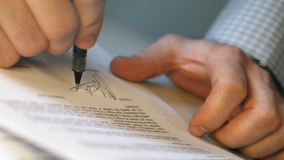 Image of a man signing an application