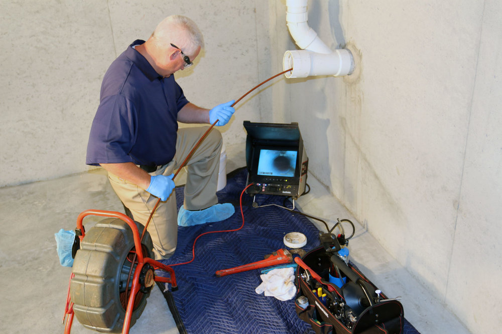 Image of a man running a sewer camera snake trhough an access pipe