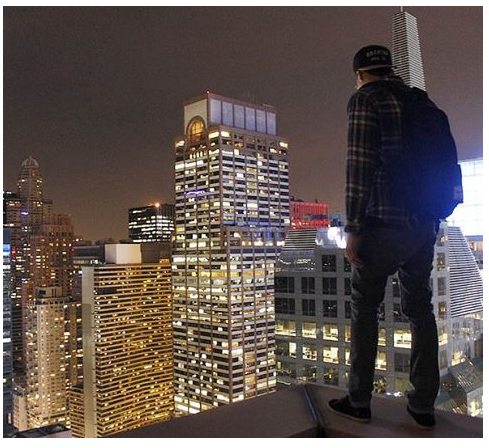 Chris standing on a ledge overlooking Manhattan.