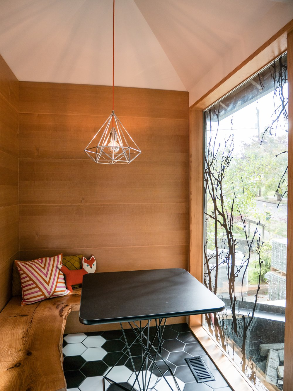 The cozy breakfast nook features built-in live-edge wood bench seating and a smaller version of the main kitchen's vaulted ceiling.
