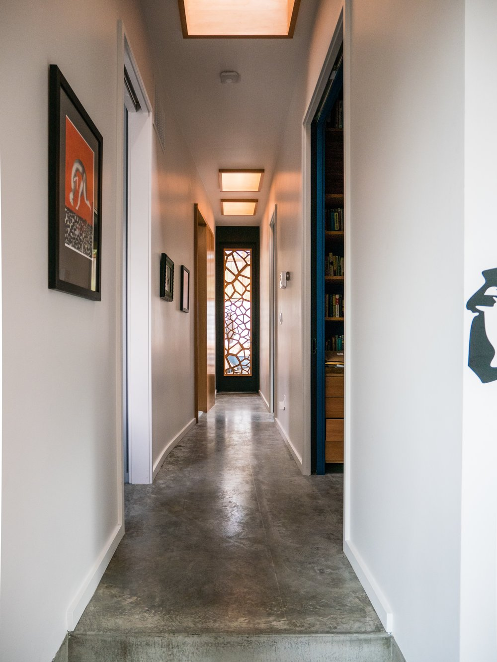 Subtle wall shifts create a hallway that is more open at its foyer entrance and tighter at the house's back door.