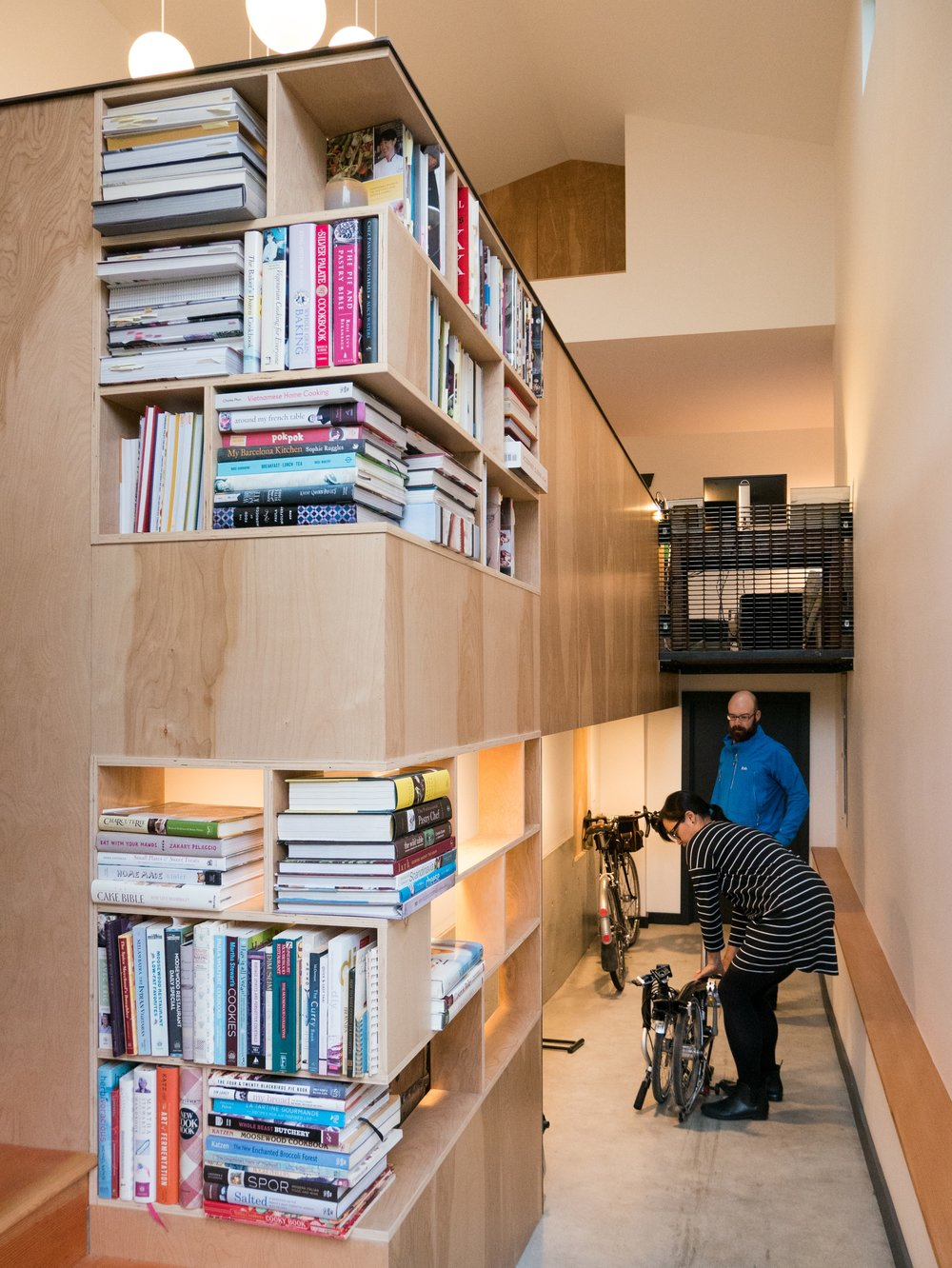 The bike ramp features a bike storage nook. The kneewall for the living area above includes cutouts for our client's expansive cookbook collection.