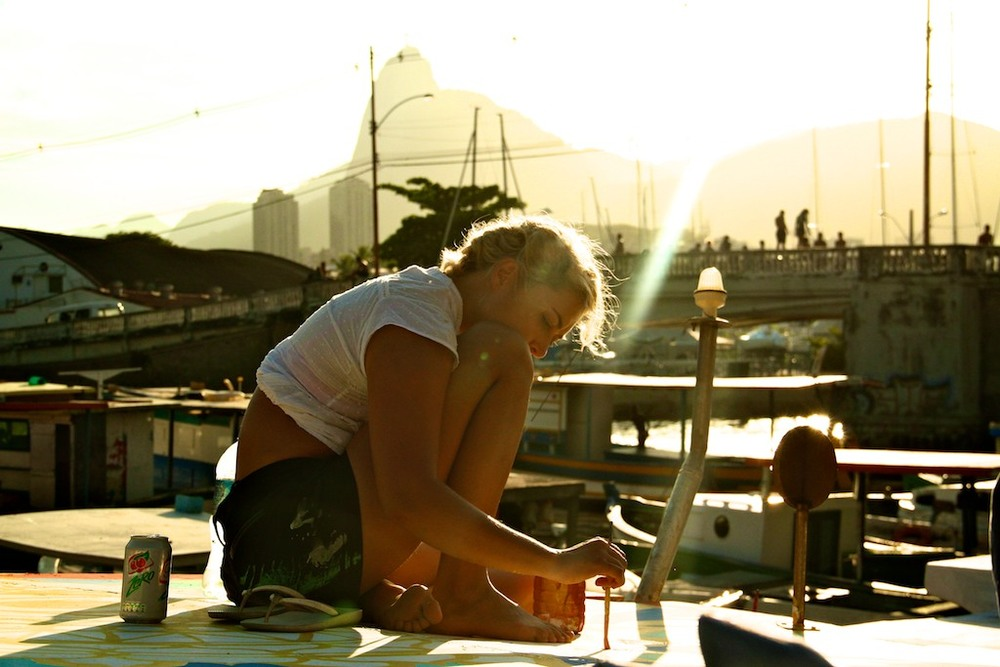 Maxine Painting a mural on a boat rooftop    In 2012, Maxine co-created  FlutuArte , a public art installation where 45 international artists joined to paint murals on the rooftops of 60 fishing boats in a historic harbor in Rio de Janeiro, Brazil. FlutuArte brought not only new vibrant colors to this fishing community, but also a new economy of tourism.