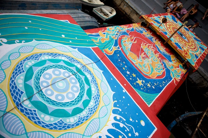 Mural collaboration between Maxine Nienow and  Nicolina     In 2012, Maxine co-created  FlutuArte , a public art installation where 45 international artists joined to paint murals on the rooftops of 60 fishing boats in a historic harbor in Rio de Janeiro, Brazil. FlutuArte brought not only new vibrant colors to this fishing community, but also a new economy of tourism.