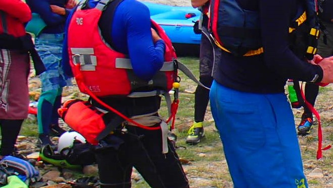 Here, both paddlers are wearing PFD mounted cow tails. The paddler to the left has a loose and oversized cow tail, presenting an entrapment hazard, while the right paddler's cow tail is snug and tight fitting.