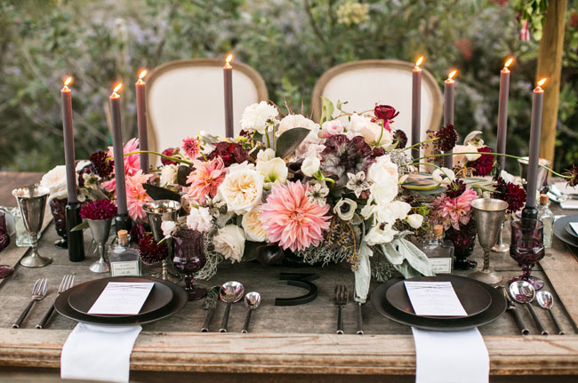 Black charger plates, pillar candles, and centerpiece bases bring a moody and romantic feel to weddings. Photo Source:  Green Wedding Shoes .