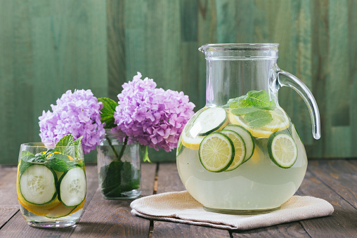 Fresh cucumber, citrus, and mint-infused water displayed in a glass water pitcher for a garden-themed bridal shower.