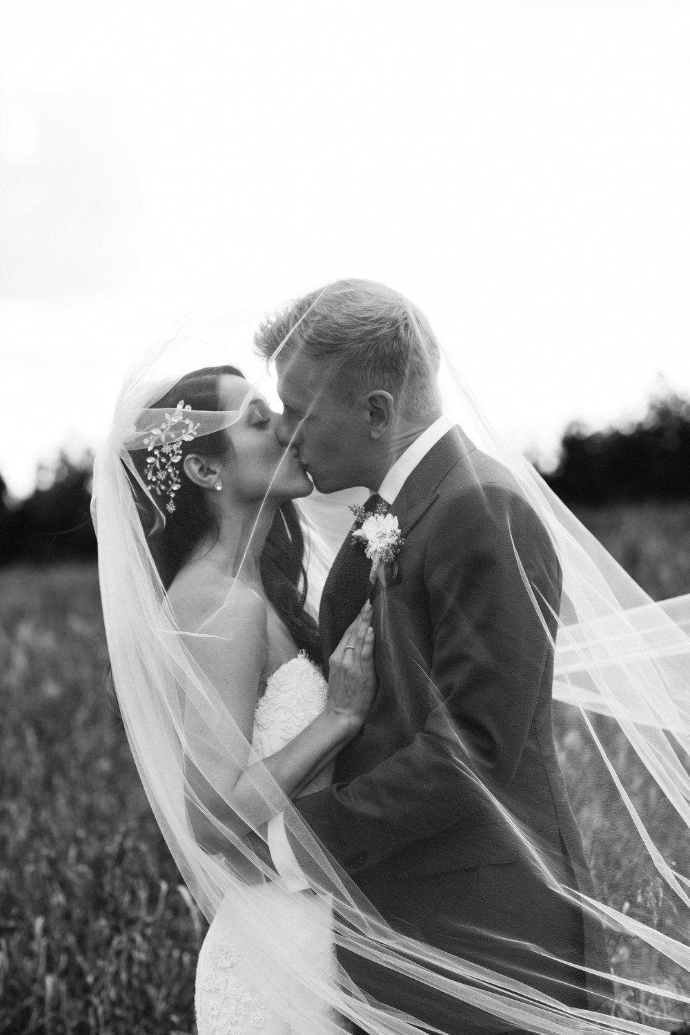 bride-groom-kissing-veil-black-white-photo