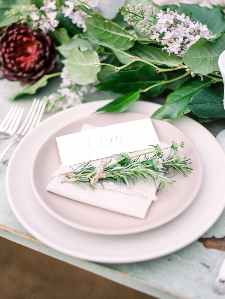 A simple and rustic table setting complete with an herb or greenery sprig exudes subtle romanticism. Photo Source:  Style Me Pretty .