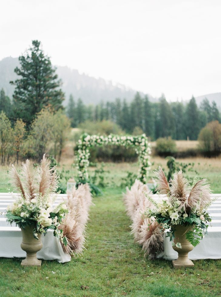 Having your outdoor ceremony aisle lined with pampas grass adds instant rustic charm, and a creative feel, to your wedding design. Photo Source:  The Knot .
