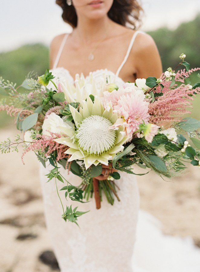 White king protea mixed with feminine dahlias and roses is a unique bridal bouquet arrangement. Photo Source:  Brides .