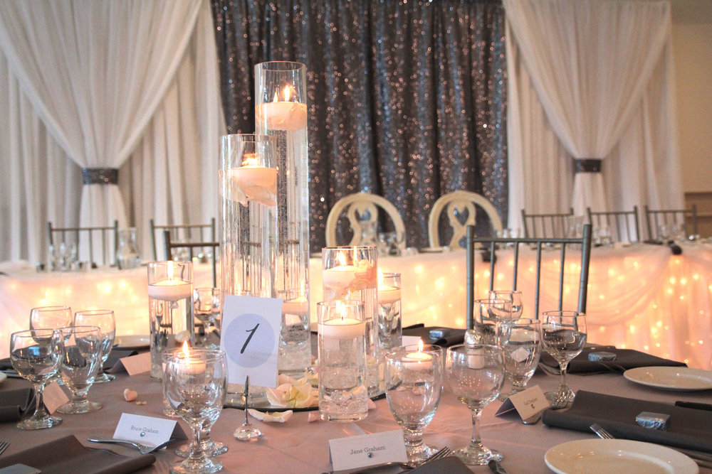 ballroom-reception-backdrop-sequin-candles-bride-groom-chairs.jpg