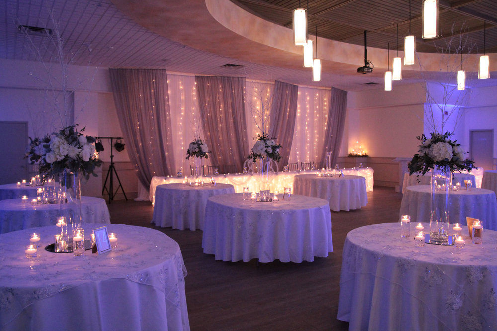 An all-white winter wonderland theme adds instant glamour to the wedding reception, especially with flickering candlelight, glowing string lighting, and sparkling sequin table overlays. Venue:  St. Marys Golf & Country Club . Decor & Styling:  Above & Beyond Event Design .