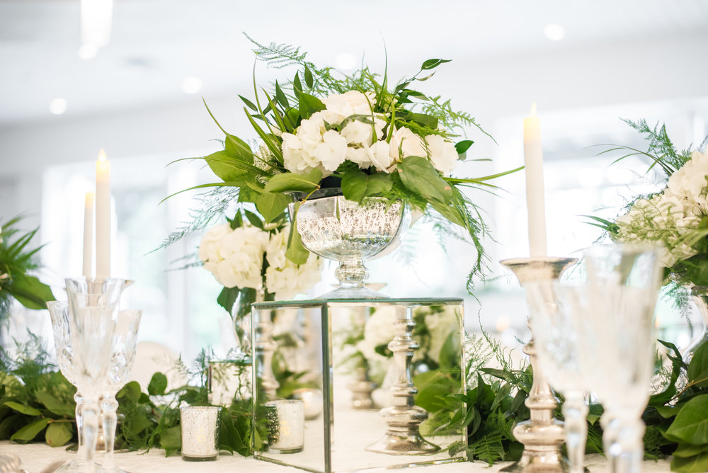 Lyric Flowers elevated the Ballroom design with an abundance of white floral and greenery, arranged in low mercury dish centerpieces, raised in glass urns, and laced through chandeliers.