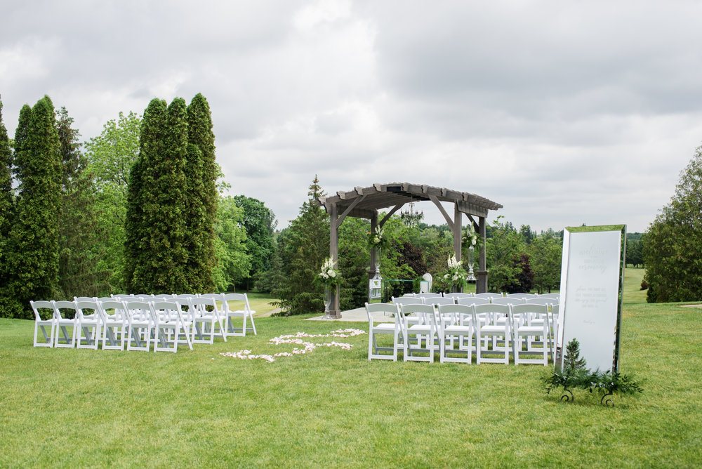 The elegant ceremony setup at our Ballroom pergola proves that classic details like white garden chairs and a rose petal aisle will always be a beautiful choice.