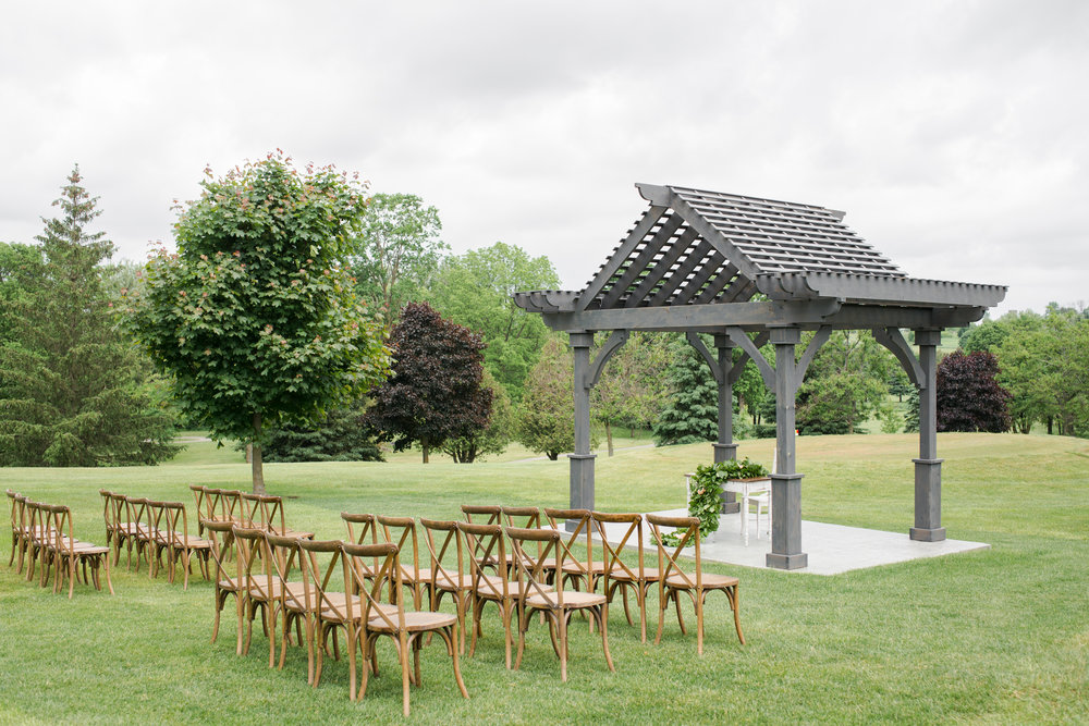 Allowing the natural beauty of the surrounding landscape to shine, we simply and organically styled the Hideaway ceremony pergola with wooden cross-back chairs and an antique signing table.