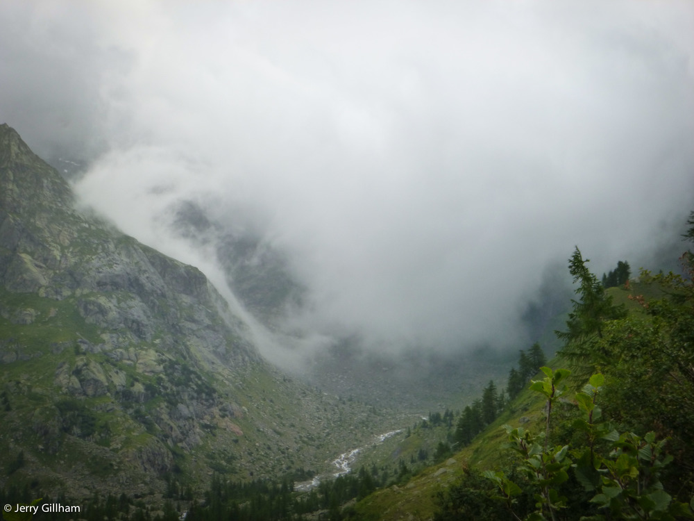 Clouds pouring over the col and into the head of the valley, swirling round like a waterfall.