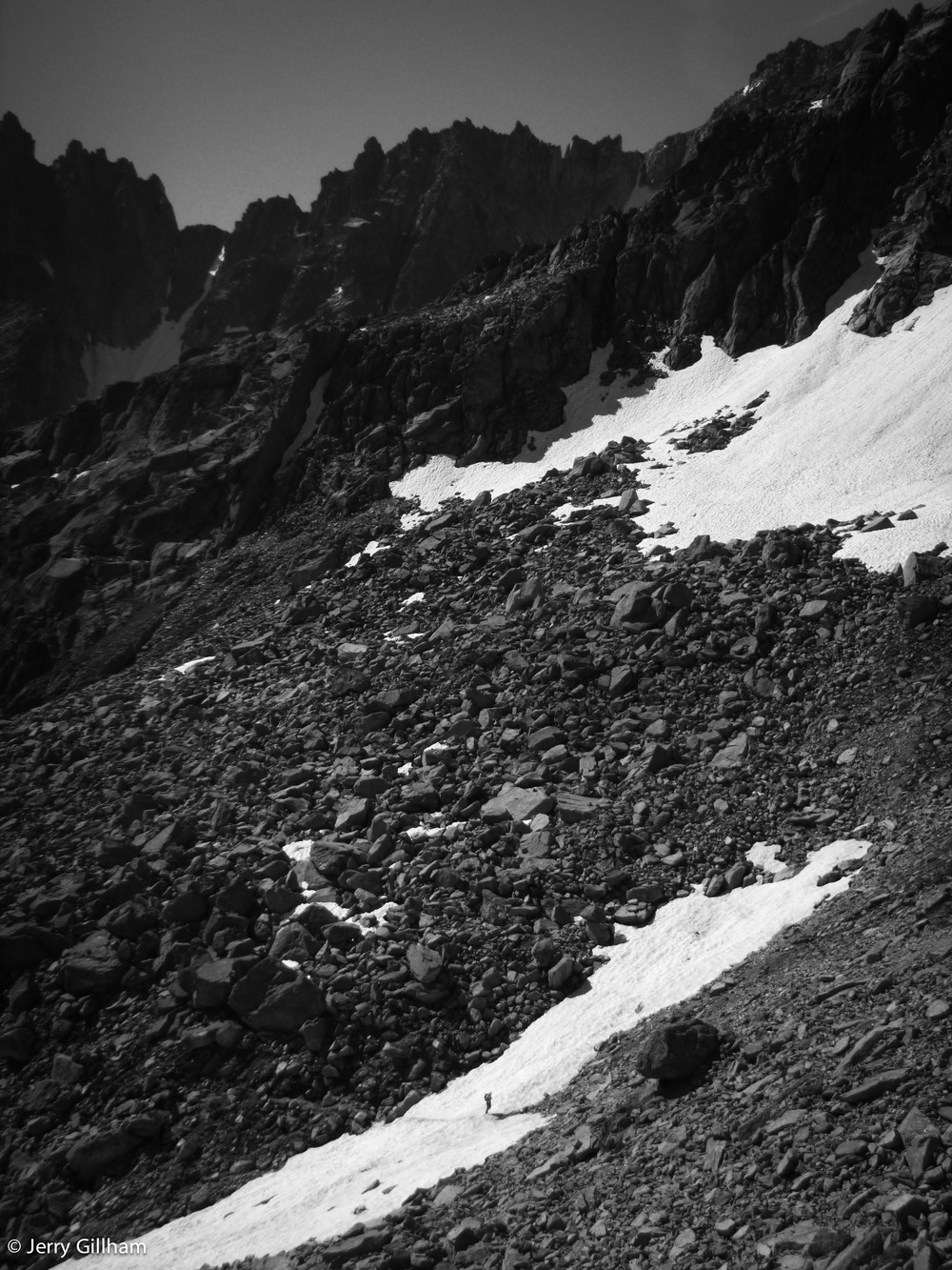 A tiny figure pushing onwards across the snow patch gives the boulders a sense of scale.