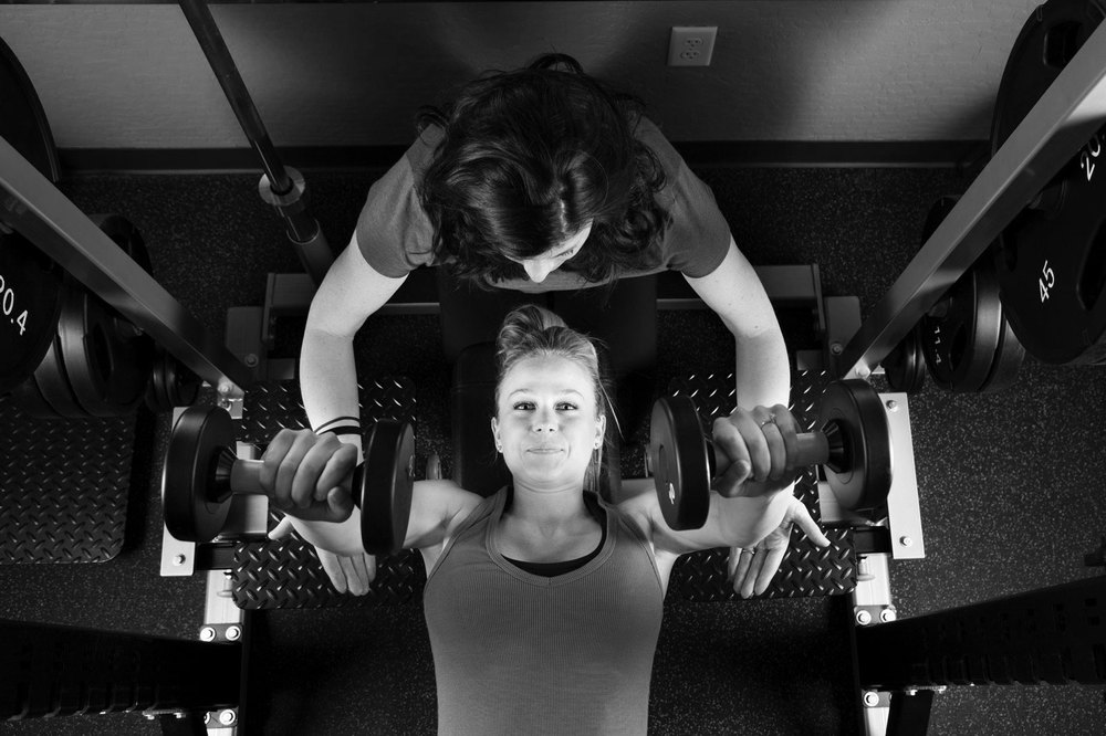 Young Woman Lifting Weights with Personal Trainer.jpg
