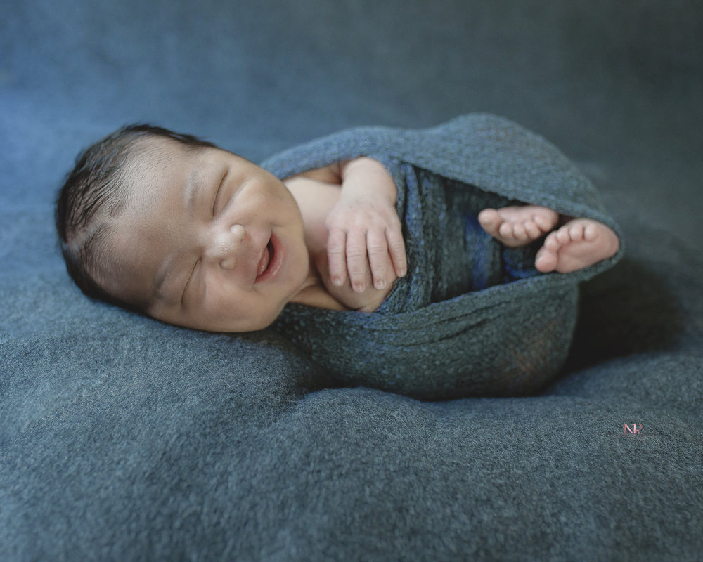 Smiling Newborn Baby Boy bathed in blue