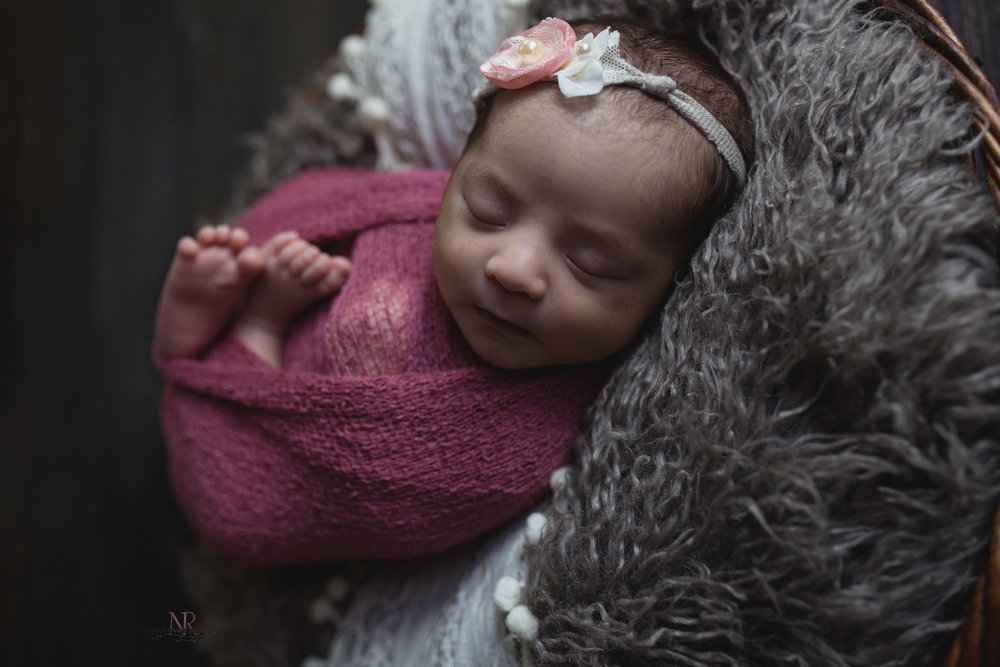Portrait if newborn baby girl wrapped in red