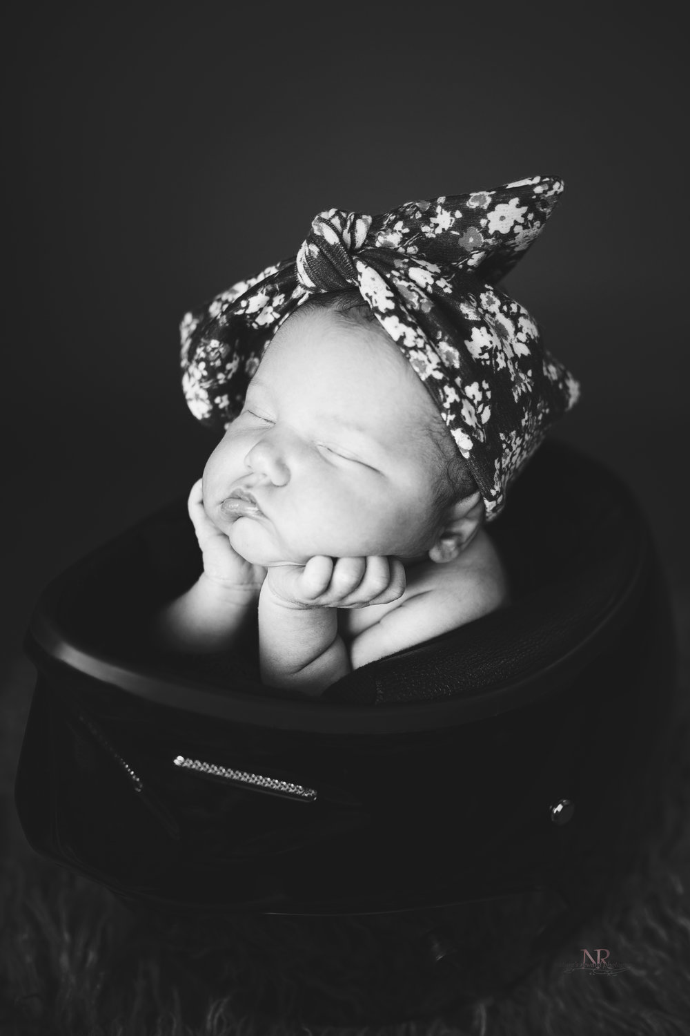 Newborn Profile portrait in black and white of baby girl in her dad's motorcycle helmet taken by Nature's Reward Photography