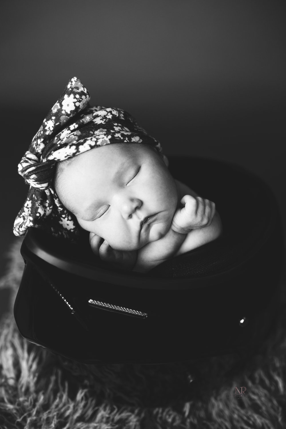 Newborn close up portrait in black and white of baby girl in her dad's motorcycle helmet taken by Nature's Reward Photography