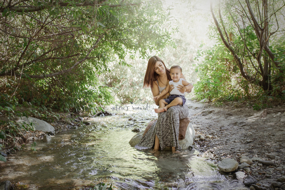 Mother and Son wading in the creek, sitting on a rock.  Image by Nature's Reward Photography, a Southern California newborn, family and child photographer