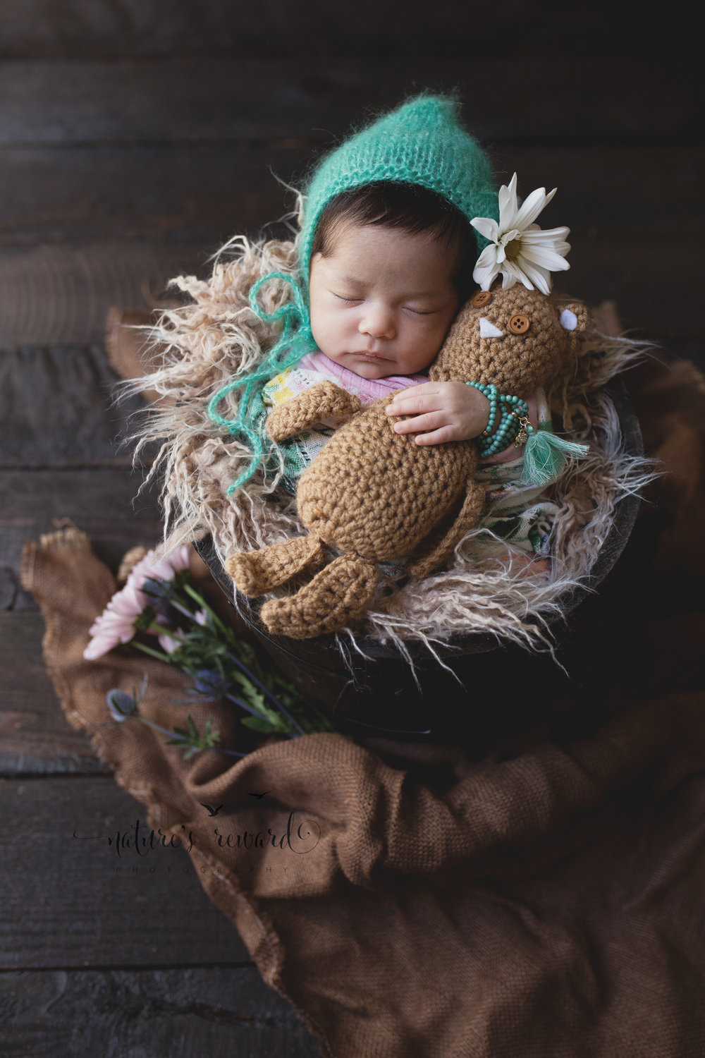 And the light and the burlap, the flowers, the daisy in her bonnet and the teddy pulling in the browns and then the magic happened in this newborn image. Image by Nature's Reward Photography