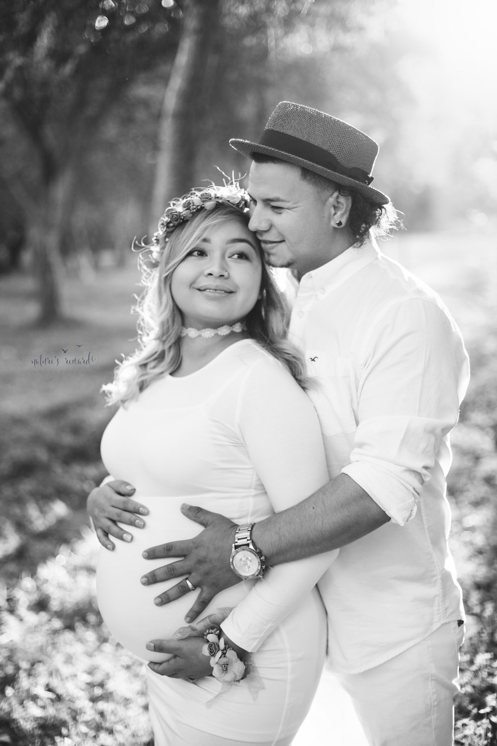 Beautiful light on this lovely couple wearing white in this black and white portrait.  Lovely white maternity gown and soft colored flower crown, while father to be wears white jeans white button up and a stunning hat to compliment the flower gown in this close pose by Nature's Reward Photography.