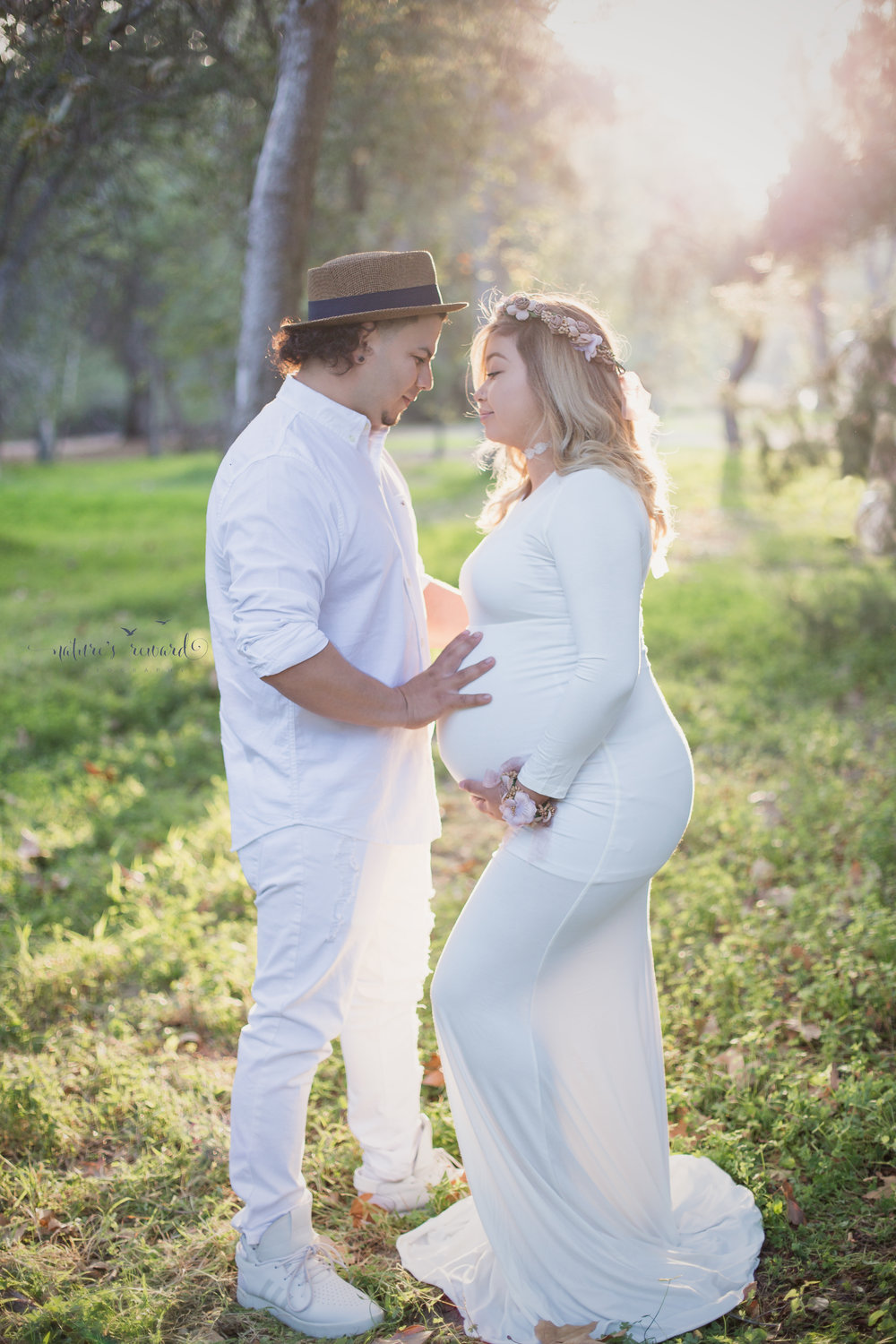 Beautiful light on this lovely couple wearing white.  Lovely white maternity gown and soft colored flower crown, while father to be wears white jeans white button up and a stunning hat to compliment the flower gown in this close pose by Nature's Reward Photography.