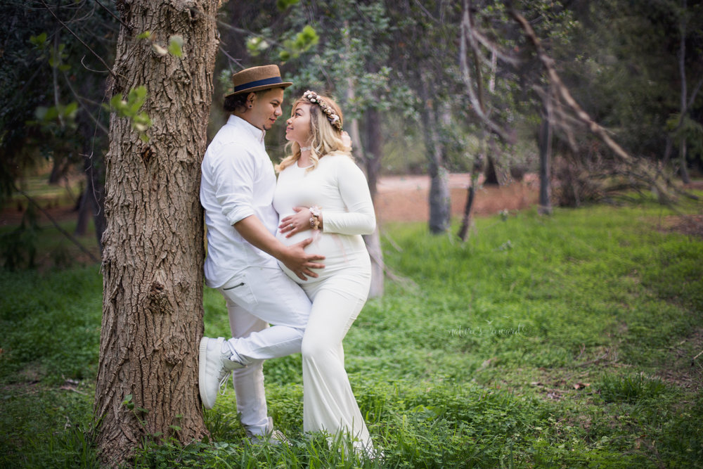 Gorgeous couple making loving connection while posing for this maternity session while wearing white- including a gorgeous white maternity gown in this portrait by Nature's Reward Photography