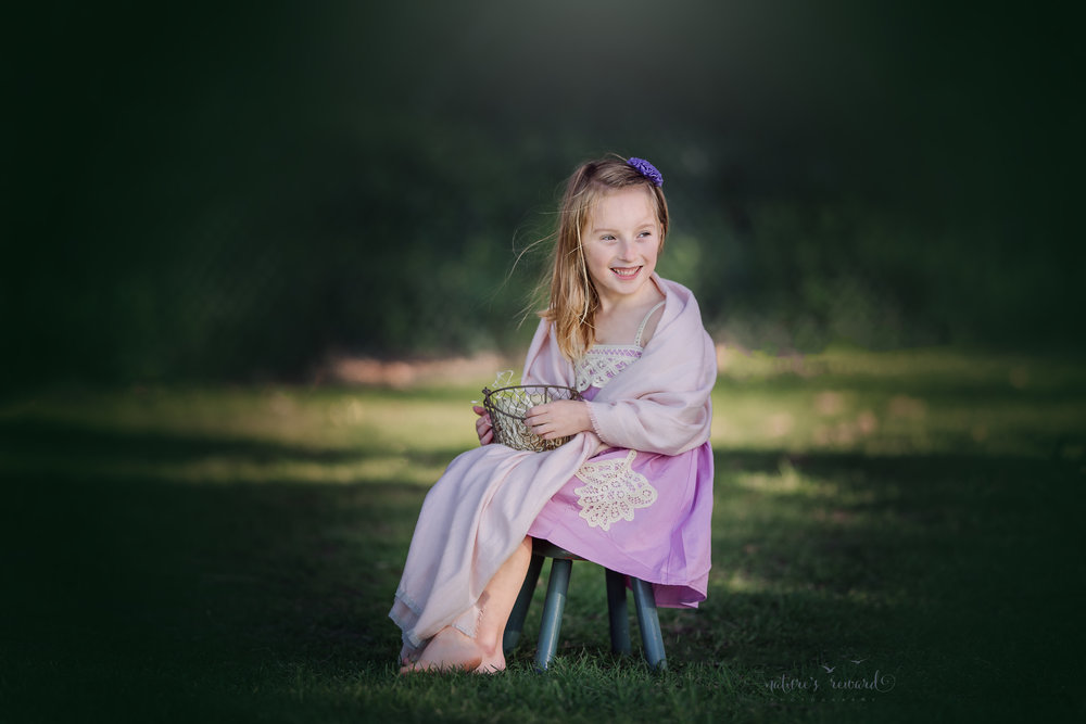 Holding a basket of eggs and wrapped in a pink shawl while wearing a a pretty purple dress this sweet girl smiles and the wind catches her hair by Nature's Reward Photography, a Southern California Photographer