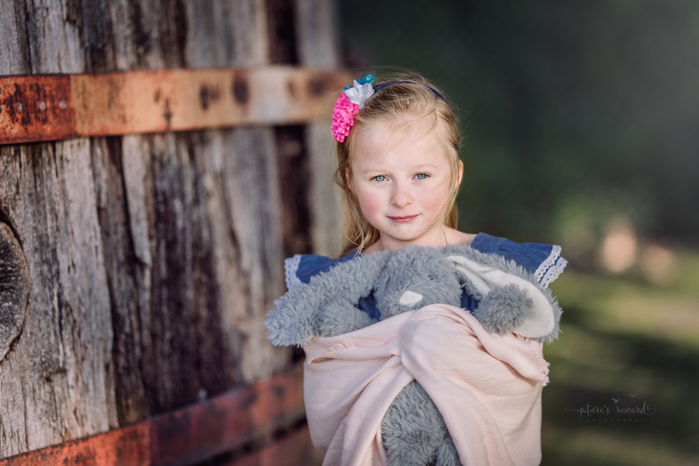The soulful look while this sweet girl wearing a blue dress wraps her arms and shawl around this long eared bunny has me in the heart strings  by Nature's Reward Photography, a Southern California Photographer