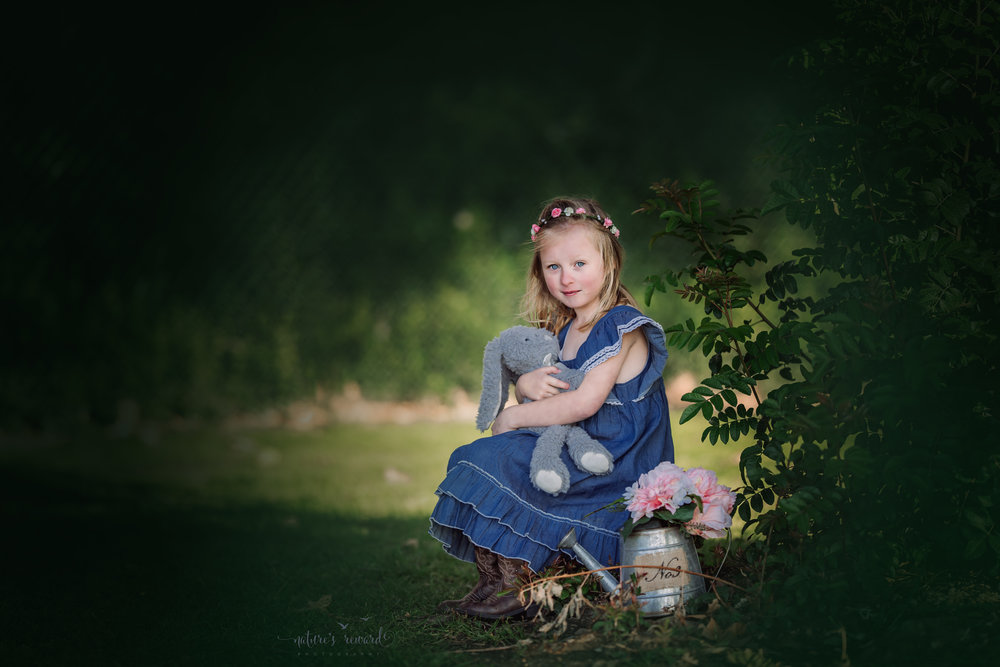 This sweet girl dressed in blue and cowgirl boots wearing a flower crown and cuddling this long eared rabbit gives the most sweetest smile in this spring portrait  by Nature's Reward Photography, a Southern California Photographer