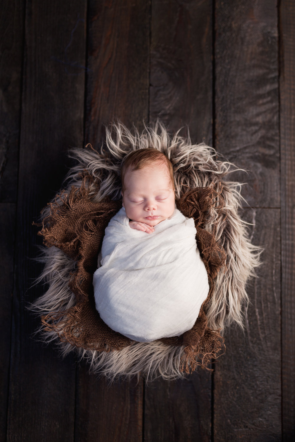 The portrait of a baby boy swaddled in white on a bed of furs and burlap in bowl on a wood floor by Southern California newborn and family photographer Nature's Reward Photography