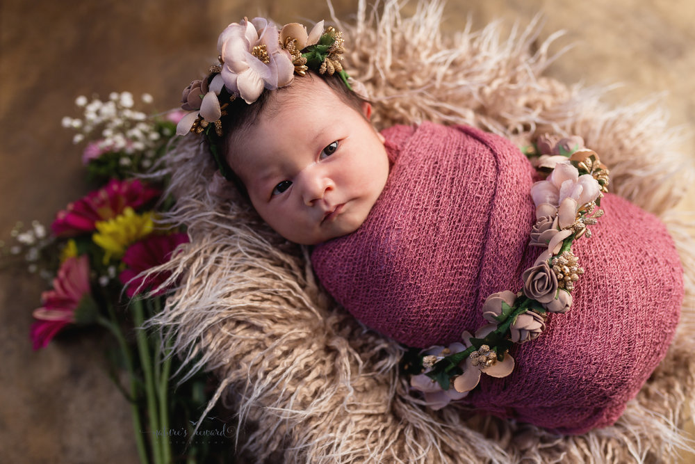 Newborn Baby Girl in rose pink wearing her flower crown laying on a basket of fur on golds and flowers in this lovely portrait by Southern California Newborn and Family Photographer Nature's Reward Photography