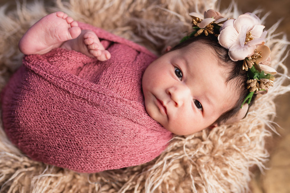 She is wide awake in this amazing portrait where this sweet newborn baby girl makes a lovely connection with the viewer while being swaddled in rose pink wearing a flower crown on a bed of furs accented by gold by Southern California Newborn and Family Photographer Nature's Reward Photography
