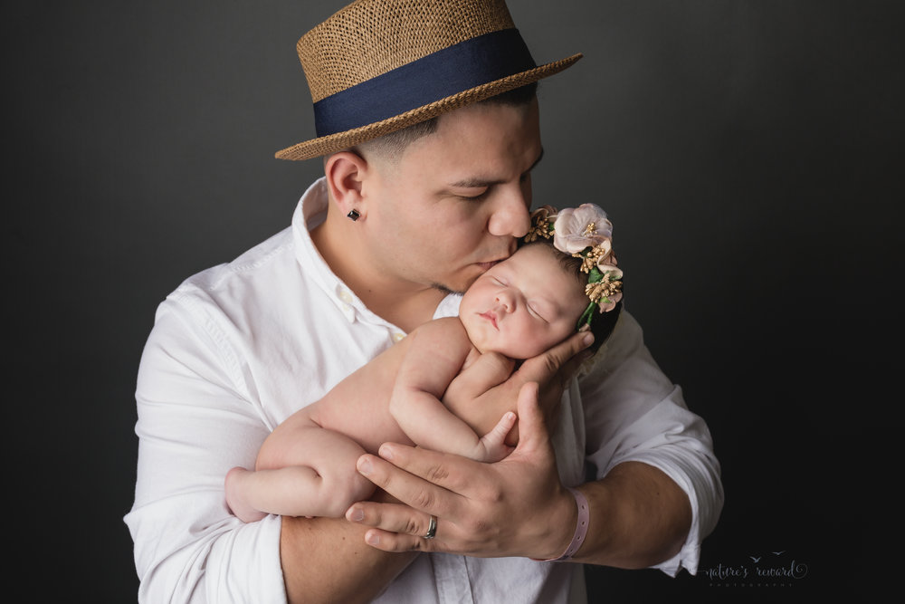 With her dad, wearing just a flower crown, she is kissed in this adorable pose by Southern California Newborn and Family Photographer Nature's Reward Photography