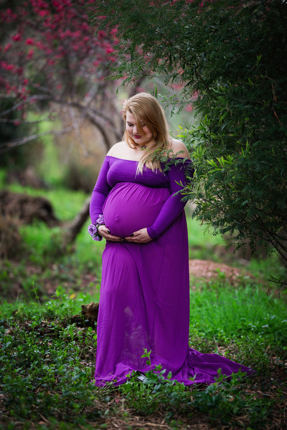 Maternity portrait of this beautiful expecting mother in a open front purple maternity gown and a beautiful lush park with cherry blossoms in Redlands Ca. by San Bernardino based photographer Nature's Reward Photography.