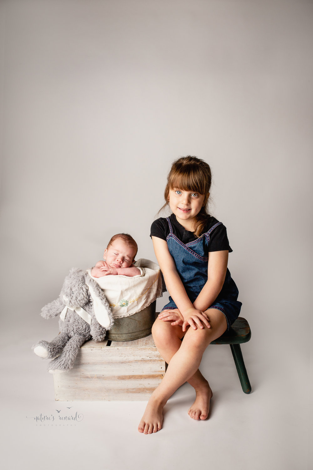 Sibling portrait with newborn on a box in a pail and showing darling kissing lips with his pal the rabbit sitting next to him is his sister with beautiful eyes in this portrait by Nature's Reward Photography