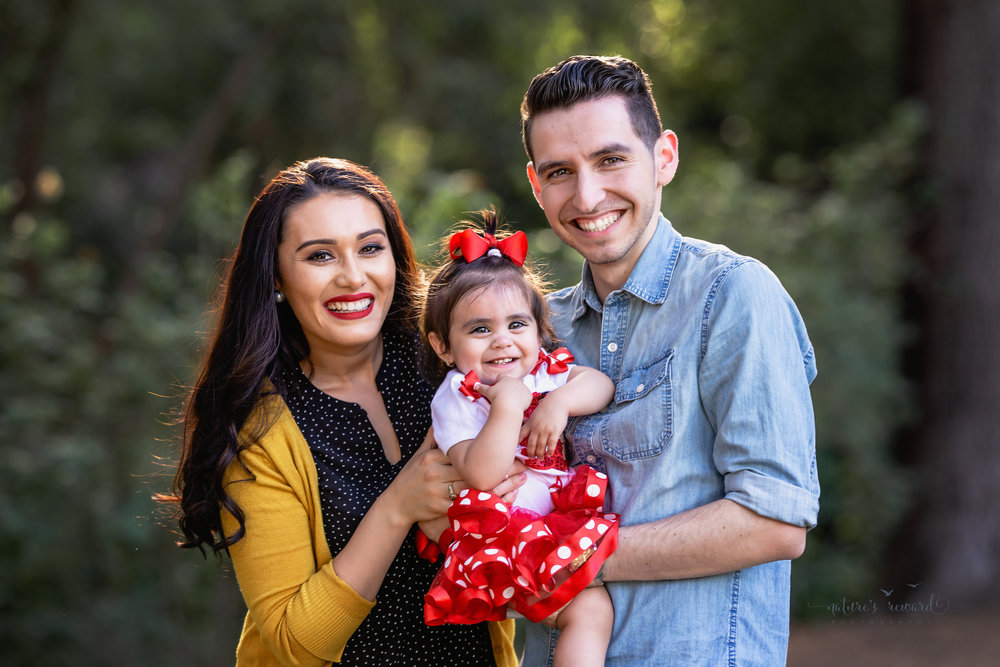 Gorgeous family close up with mom in a black pok a dot blouse and yellow cardigan and dad in a denim button down shirt with baby girl in a mickey inspired shirt and tutu in this portrait by Nature's Reward Photography.