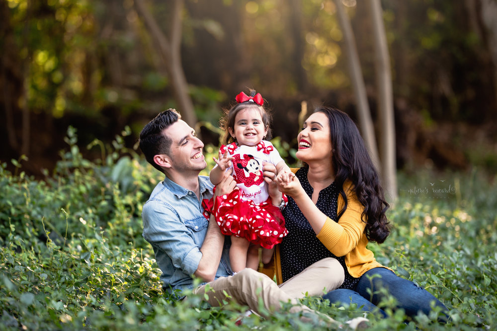 Darling loving family with mom in a black pok a dot blouse and yellow cardigan and dad in a denim button down shirt with baby girl in a mickey inspired shirt and tutu in this portrait by Nature's Reward Photography.